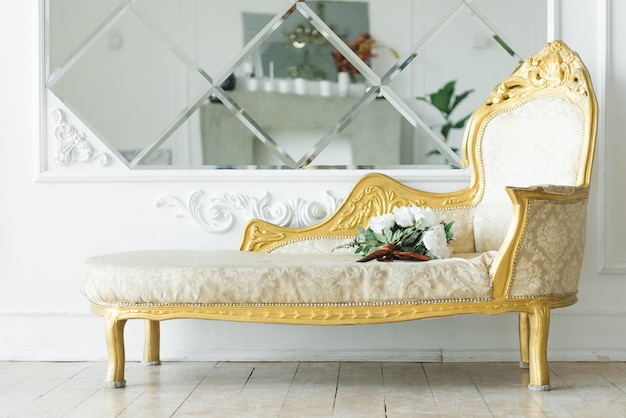 Luksusowa sofa vintage ze złotem w pobliżu lustra, piękne klasyczne wnętrze