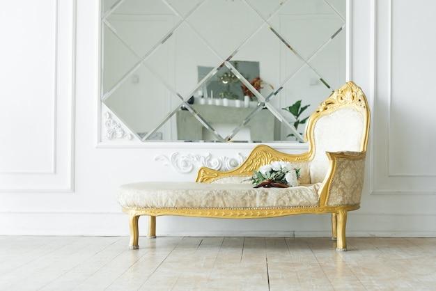 Luksusowa sofa w stylu vintage ze złotem w pobliżu lustra