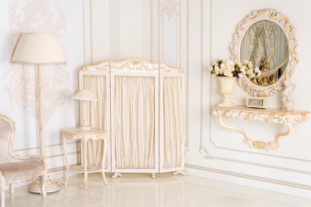 Luksusowa sypialnia w jasnych kolorach z lustrem i składanym parawanem. eleganckie klasyczne wnętrze