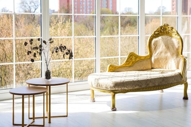 Luksusowa złota kanapa na tle dużego okna.