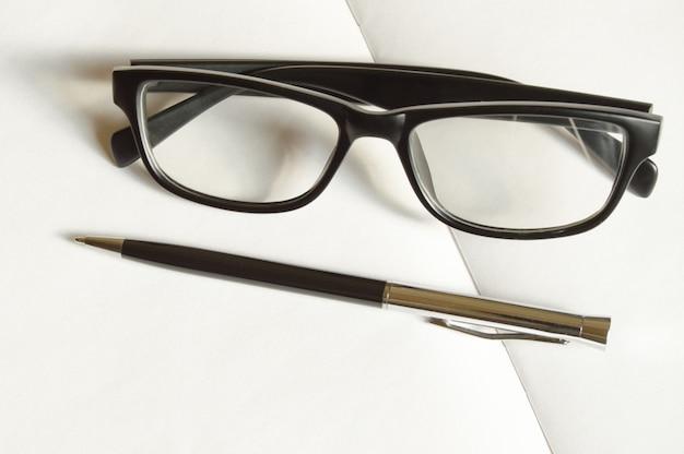 Luksusowe akcesoria męskie - stylowe czarne okulary i długopis na białej powierzchni biurka