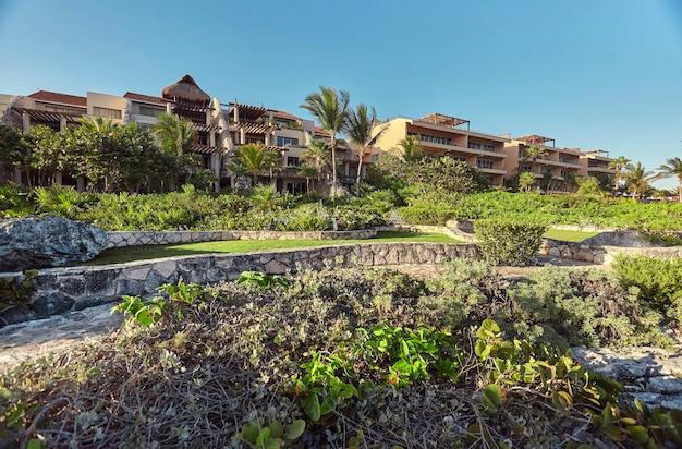 Luksusowe apartamentowce zanurzone w tropikalnej roślinności na skalistym wybrzeżu puerto aventuras w meksyku