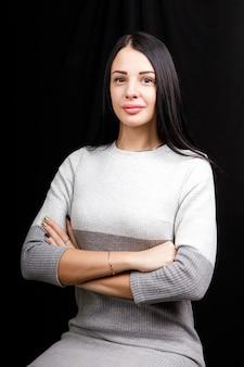 Luksusowe ciemnobrązowe proste włosy brunetki kobiece moda brązowe oczy skrzyżowane ręce na co dzień wygląd zmysłowe czarne tło.