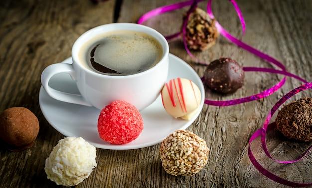 Luksusowe cukierki czekoladowe i filiżanka kawy