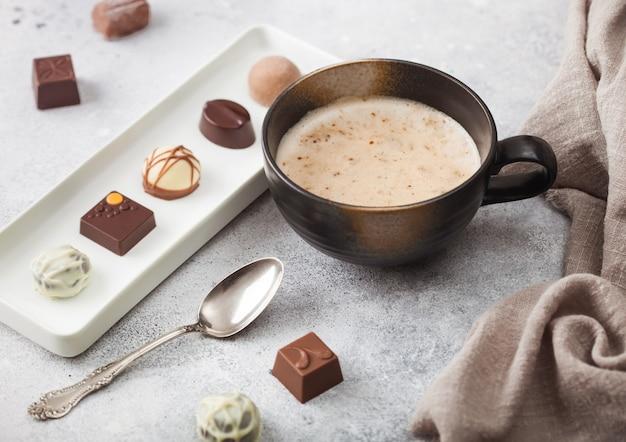 Luksusowe cukierki czekoladowe na białym porcelanowym talerzu z filiżanką kawy cappuccino i srebrną łyżeczką
