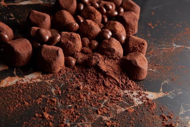 Luksusowe czekoladowe trufle na czarnym marmurowym tle.