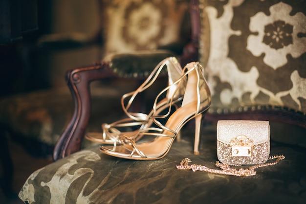 Luksusowe dodatki damskie, złote buty na obcasie, mała torebka wieczorowa, elegancki styl, styl vintage, sandały obuwie