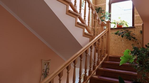 Luksusowe drewniane schody do sypialni na drugie piętro w wiejskim domu lub willi.
