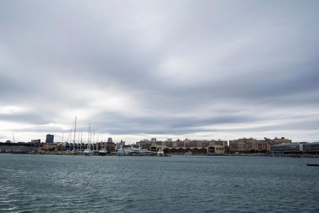 Luksusowe jachty i łodzie w porcie w walencji na morzu śródziemnym. refleksja w wodzie. białe jachty są na początku wiosny w hiszpańskim porcie w walencji. pochmurne niebo.