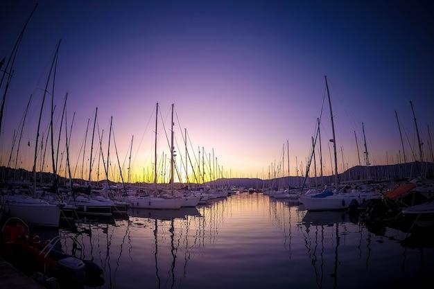 Luksusowe jachty zacumowane w porcie morskim o kolorowy zachód słońca morski parking łodzi motorowych