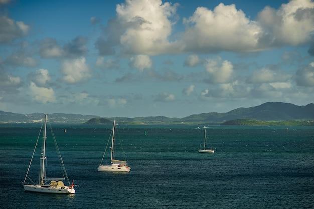 Luksusowe jachty zakotwiczone w błękitnej wodzie z fortem w tle.