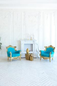 Luksusowe jasne wnętrze salonu ze złotą ścianą i szykownymi drogimi meblami w biało-złotych kolorach