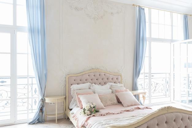 Luksusowe jasne wnętrze w stylu barokowym. przestronny pokój z pięknymi, drogimi meblami, kominkiem i kwiatami. stiuk roślinny na ścianach i parkiet z jasnego drewna
