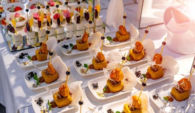Luksusowe jedzenie na weselnym stole. małe przekąski na białych talerzach. surowe z przekąskami. zbliżenie.