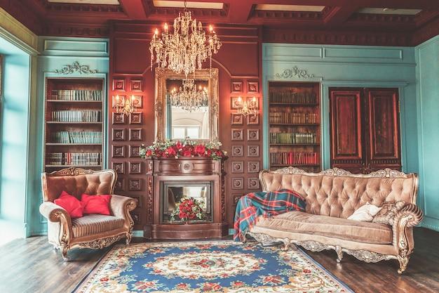 Luksusowe klasyczne wnętrze domowej biblioteki. salon z półką na książki, książkami, fotelem, sofą i kominkiem