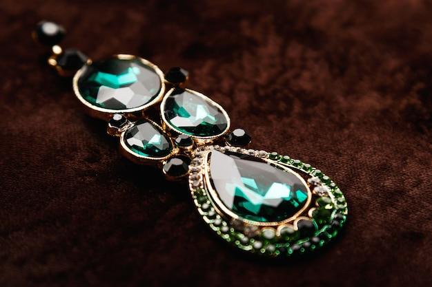 Luksusowe kolczyki z zielonymi kamieniami na brązowym aksamicie