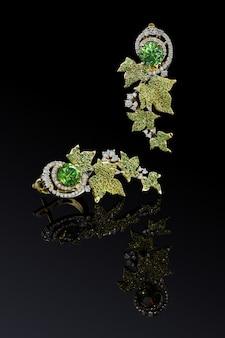 Luksusowe kolczyki z żółtego złota z zielonymi demantoidami i diamentami na białym tle na czarnym tle z odbiciem, zawiera ścieżkę przycinającą. ekstremalne zbliżenie.