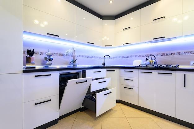 Luksusowe nowoczesne klasyczne białe wnętrze kuchni, większość drzwi i szuflad jest otwarta