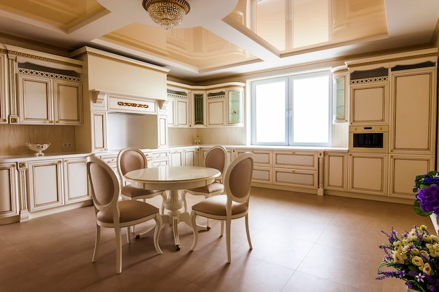 Luksusowe, nowocześnie wyposażone wnętrze kuchni. kuchnia w luksusowym domu z beżowymi szafkami. stół i krzesła