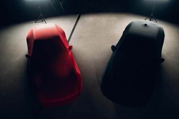Luksusowe samochody sportowe w pokrowcach w garażu.