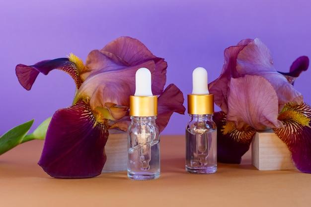 Luksusowe spa naturalne organiczne produkty do pielęgnacji skóry na tle papieru. butelki z zakraplaczem z olejkiem eterycznym lub olejkiem do masażu aromaterapeutycznego, kwiaty irysa. pielęgnacja ciała, koncepcja leczenia skóry.