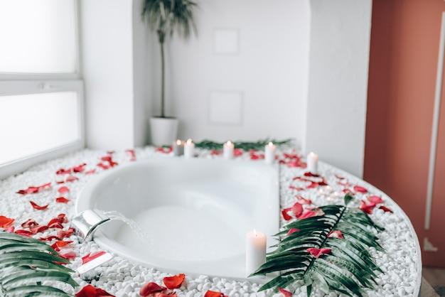 Luksusowe wnętrze łazienki ozdobione gałązkami palmowymi i płatkami róż, nikt