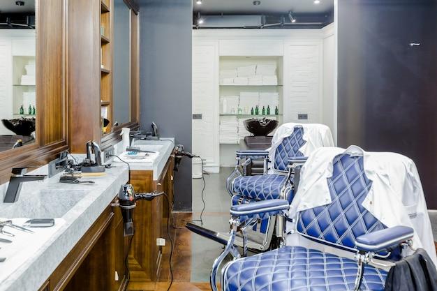Luksusowe wnętrze salonu fryzjerskiego, drogie niebieskie meble, wykończenia z drewna, modny czarny sufit