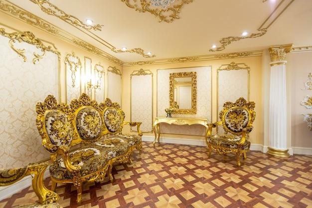 Luksusowe wnętrze salonu z pięknymi starymi rzeźbionymi meblami w kolorze złotym z dekoracjami na ścianach w stylu pałacu królewskiego