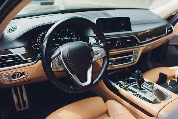 Luksusowe wnętrze samochodu. kierownica, dźwignia zmiany biegów i deska rozdzielcza.