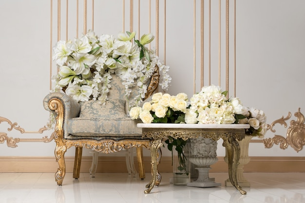 Luksusowe wnętrze vintage w arystokratycznym stylu z eleganckim fotelem i kwiatami. retro, klasyka.
