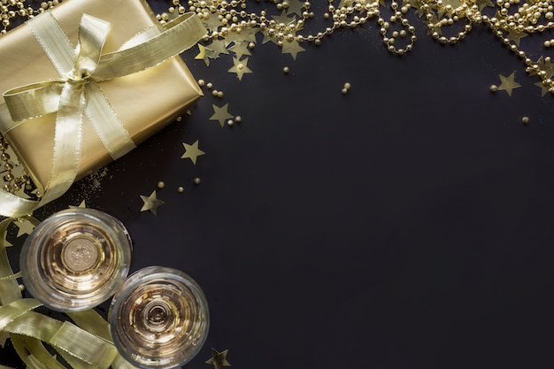 Luksusowe złote pudełko z dwoma lampkami szampana na czarnym tle. przyjęcie bożonarodzeniowe. leżał płasko. widok z góry. boże narodzenie.