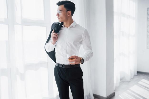 Luksusowo wyglądający mężczyzna w klasycznym stroju stoi w pokoju i trzyma górę garnituru i szklankę z alkoholem.