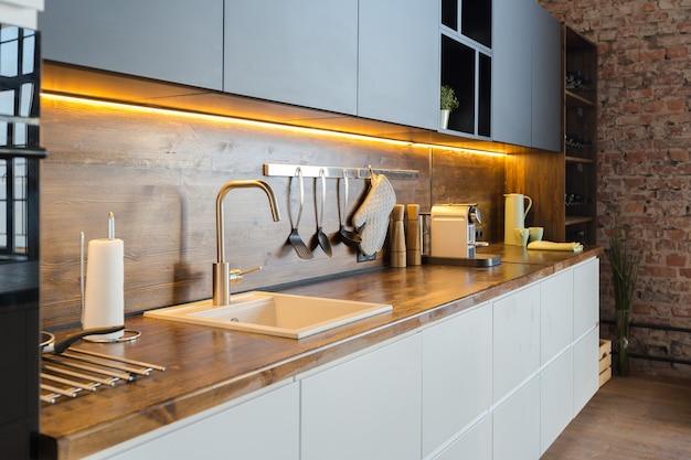 Luksusowy apartament w stylu loftowym w ciemnych kolorach. stylowa nowoczesna kuchnia z wyspą
