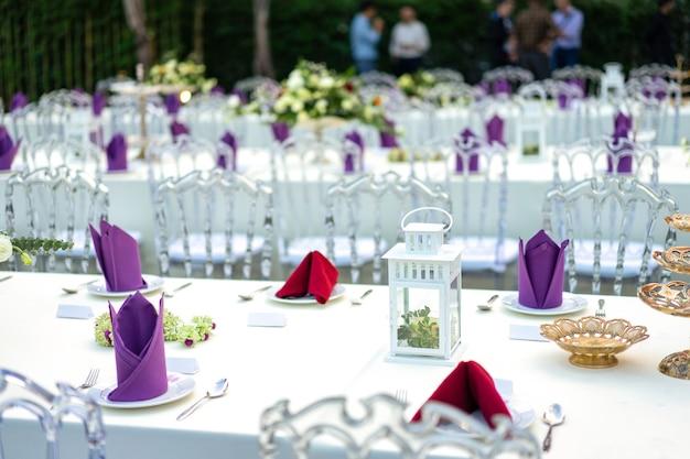 Luksusowy biało - fioletowo - czerwony stół obiadowy z kryształowym krzesłem w ogrodzie.