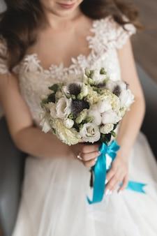 Luksusowy biały ślubny bukiet w rękach panny młodej