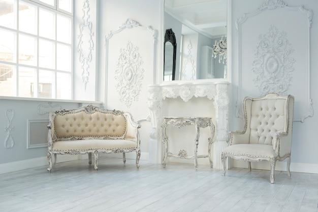 Luksusowy, bogaty wystrój salonu z eleganckimi klasycznymi meblami i dekoracjami ściennymi. duży, jasny, biały pokój z dużym oknem