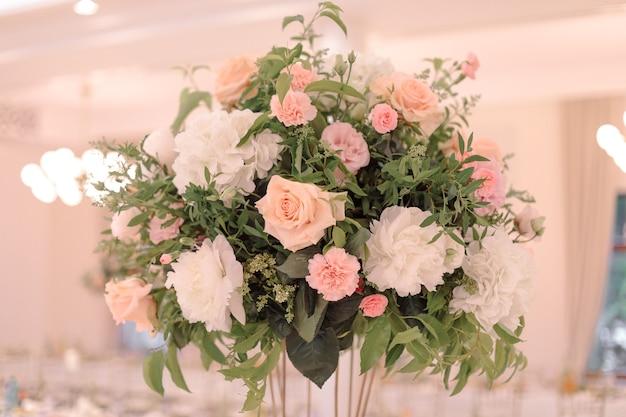 Luksusowy bukiet kwiatowy na prezydium weselne, wykonany w delikatnych odcieniach różu i kremu z fakturowaną zielenią. imprezy weselne. florystyka i projektowanie. kolor różowy. świętowanie i zabawa.