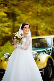 Luksusowy bukiet róż w rękach panny młodej w pięknej sukience na ulicy. młoda uśmiechnięta piękna dziewczyna o blond włosach w sukni ślubnej.