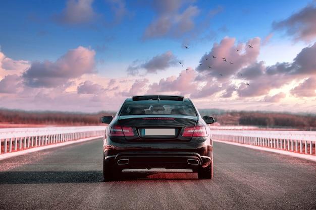 Luksusowy czarny samochód jadący ulicą z pięknym niebem