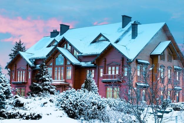 Luksusowy dom z bali, drewniany dwór pokryty śniegiem w winter park o zachodzie słońca.