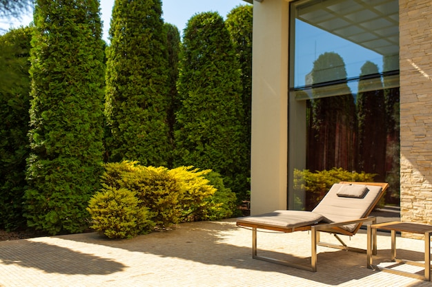 Luksusowy dom, zadbany dziedziniec z zielonym ogrodem i wygodnymi leżakami do wypoczynku w ogrodzie