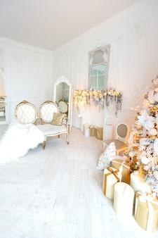 Luksusowy, drogi, jasny salon w królewskim stylu ozdobiony choinką i dużymi oknami