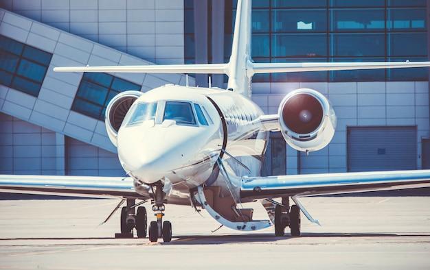 Luksusowy i błyszczący odrzutowiec biznesowy stojący na lotnisku. luksusowy styl życia i transport własnym samolotem.