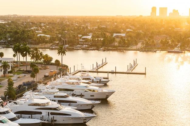 Luksusowy jacht zaparkowany na kanale ze słońcem schodzącym w fort lauderdale. port w fort lauderdale z sunset w marinie