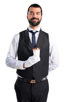 Luksusowy kelner trzyma filiżankę kawy