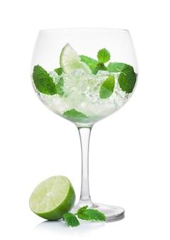 Luksusowy kieliszek letniego koktajlu alkoholowego mojito z kostkami lodu miętą i limonką na białym tle