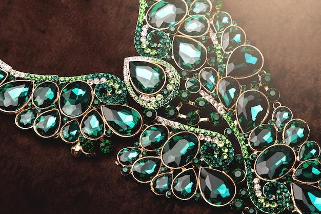 Luksusowy naszyjnik z zielonymi kamieniami na brązowym aksamicie