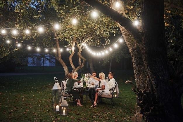 Luksusowy obiad. porą wieczorową. przyjaciele jedzą kolację w pięknym miejscu na świeżym powietrzu