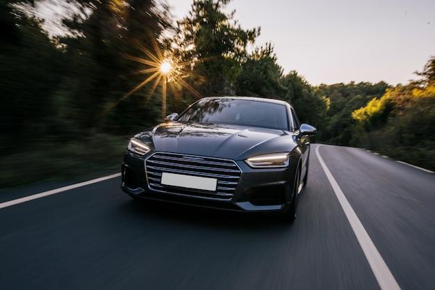 Luksusowy samochód sportowy ze światłami ksenonowymi. przedni widok. jedź o zachodzie słońca.