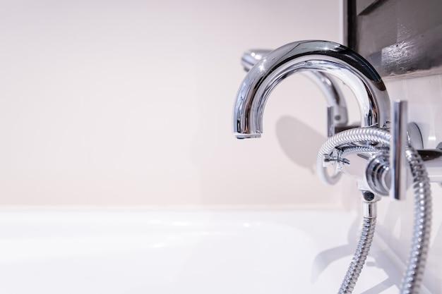 Luksusowy srebrny kran z ciepłą i zimną wodą i głowica prysznicowa do wanny w łazience z bliska. koncepcja opieki zdrowotnej i odnowy biologicznej.